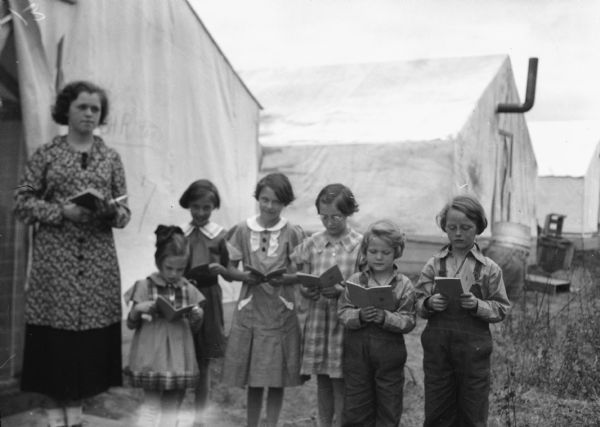 "One of two images under the headline: ""How Children Keep Busy in Alaskan Tent Colony."" Original caption reads: ""How do the children live in the Wisconsin-Michigan-Minnesota Alaskan colony? These pictures supply part of the answer. Here, for instance, Bernadine Reitan, 15, of Superior, conducts Sunday school in front of her parents tent."" Evelyn, 5, and Margaret Foster, 8, are in overalls on the right."