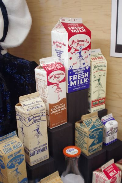 "Display of Matanuska Maid Milk Products. From the Palmer Historical Society: ""Matanuska Maid"" was first the brand name of the Matanuska Valley Farmers Cooperating Association dairy products, which was later the name of the dairy. ""Anuska"" was the name given the little skater, and endearing symbol for the dairy products as well as the ""Maid,"" the place where it all began."