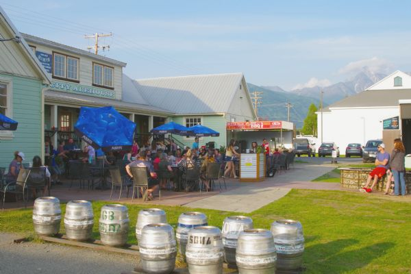 Crowd of people on a patio at the Alehouse in Palmer. The building used to be the part of the cooperative. The buildings of the Matanuska Valley Farmers Cooperating Association included a trading post, creamery, and warehouse, plus numerous other businesses.