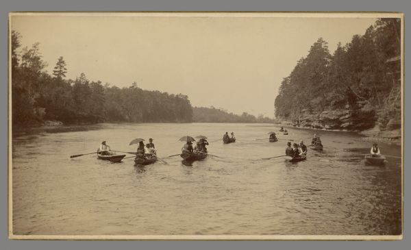 Fleet of rowboats carrying men and women with umbrellas.