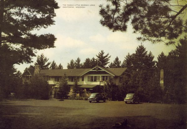 Exterior view of the lodge. Cars are parked in front, and a man is standing among trees.
