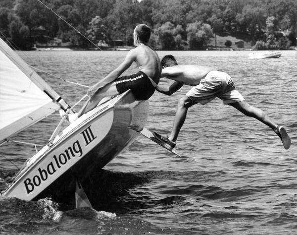 "Two boys on the class-C scow sailboat ""Bobalong III,"" with one boy balancing off the side while standing with one leg on the bilge keel."