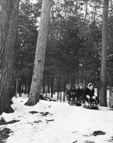 Three women and a man slide down a snowy hill on a wooden toboggan.