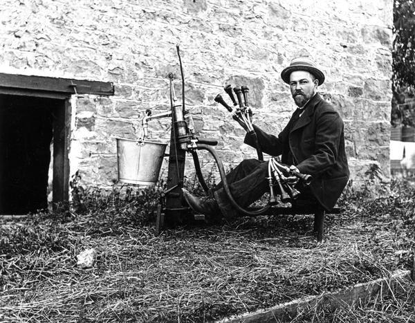 Man in hat posing with milking machine.