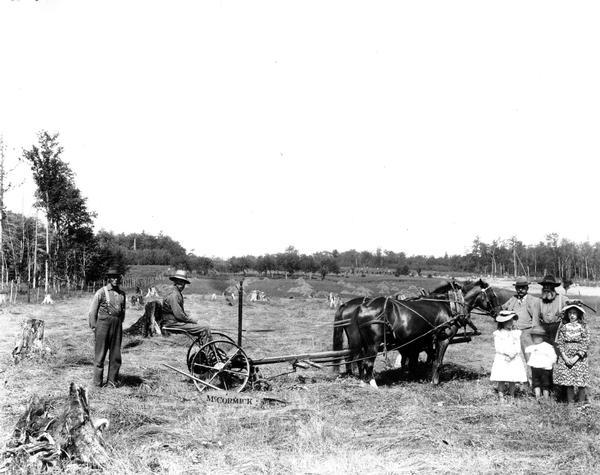 Four men and three children posing by a McCormick mower in a field.