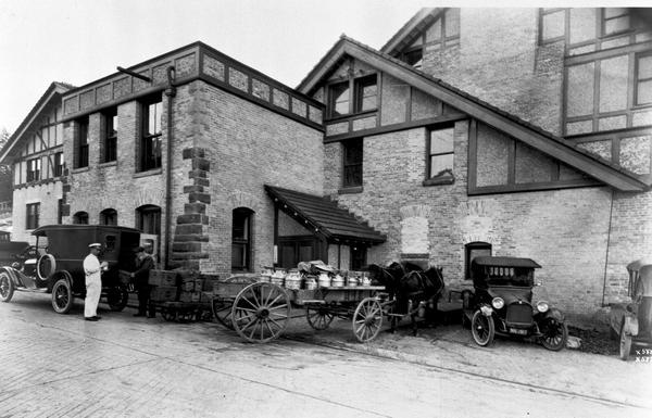 Exterior view of a dairy. Two cars and a horse-drawn wagon loaded with milk cans are parked in front of building.