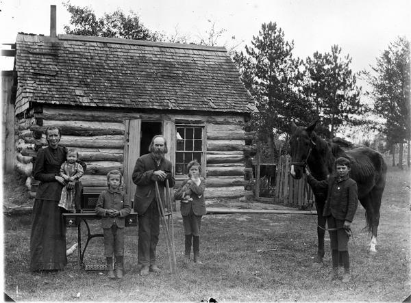 Farm family posing in front of a log home. There is a man on crutches in the center, a woman is holding a small child standing on a table, and two children standing, one holding a cat. On the right is a boy is standing and holding the bridle of a horse.