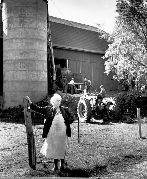 Mrs. Mary Shaughnessy standing in front of barn where men are loading the silo. Her farm was on the site where Granville School was later built.