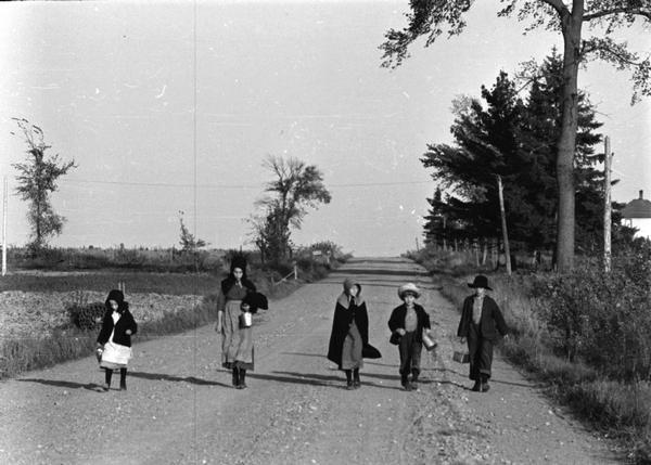 Five Mennonite children walking down the middle of the road after a fishing trip.