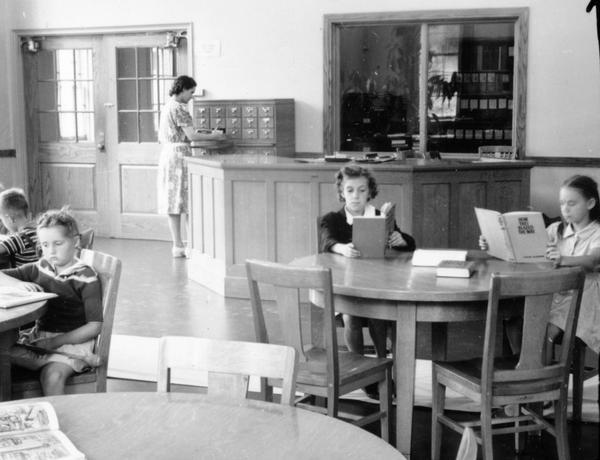 Young children reading at the library. A librarian works near the circulation desk in the background. When it opened in 1938, the Library had a seating capacity of 72 and a 5600 volume capacity, though it only had 2000 volumes at the time.