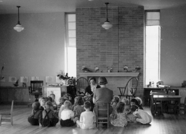 Students gathered closely around their teachers in the kindergarten room on the south end of the school. The open hearth, fireplace, high ceilings and windows all combined to create a positive learning atmosphere.