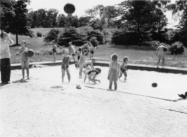 A group of children and adults at a wading pool in a park.