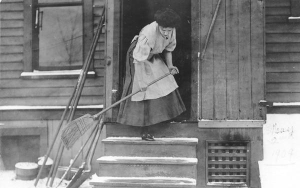 Woman sweeping snow off a porch. She is wearing a dress and apron.