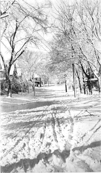 Winter scene of an unplowed, snowy Butler Street, with tire tracks and snow-covered trees.