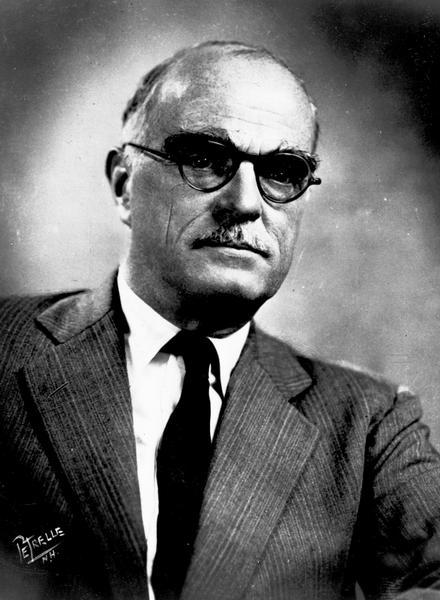Quarter-length studio portrait of Thornton Wilder wearing eyeglasses.