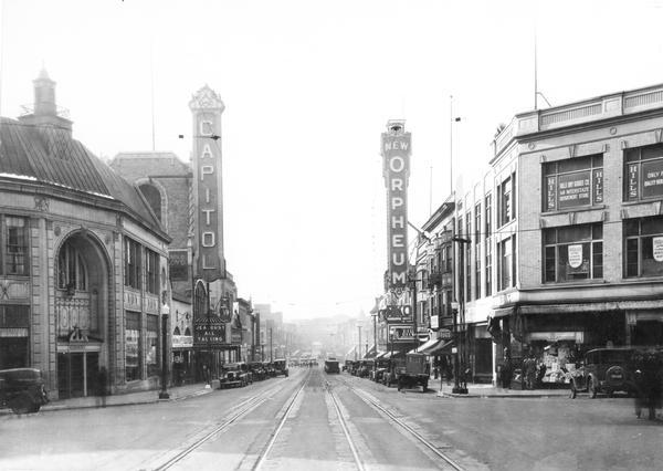 "State Street view looking toward the University of Wisconsin, with the 200 block in the foreground. The marquee for the Capitol Theatre reads ""'Jealousy,' All Talking,"" and a sign below the Orpheum Theatre's marquee reads: ""Thanksgiving Month."" Other storefronts include Rennebohm's Drugstore, Hills Dry Goods Co., and Kessenich's. In the far background is Bascom Hill of the University of Wisconsin."