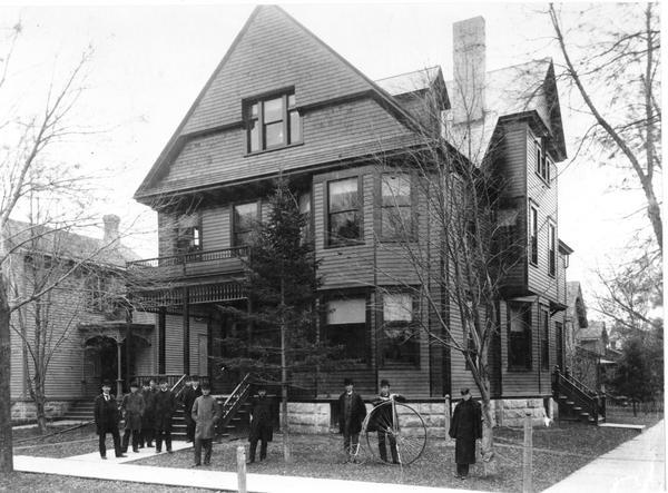 Men standing outside of the Delta Upsilon fraternity house at 673 State Street, at the intersection of State and Lake Streets. Lawrence Whittet stands to the left of the bicycle and Burt Shirley is on the far right.