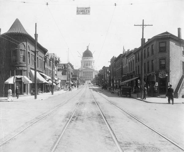 View looking up the 200 block of State Street from West Johnson Street, showing the Wisconsin State Capitol dome under construction. The bank on the left is a branch of the Bank of Madison. An overhead sign says the speed limit is 8 miles per hour.