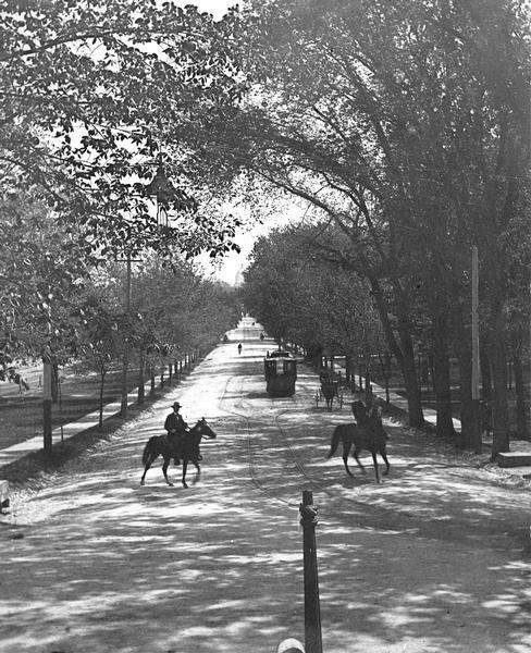 Tree-lined State Street from Bascom Hill on the University of Wisconsin-Madison campus. Traffic on State Street includes a well-dressed gentlemen on horseback and a streetcar.