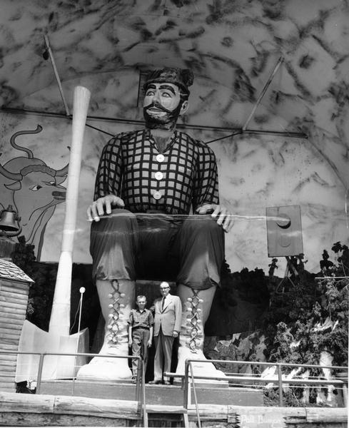 A man and boy pose in front of a giant Paul Bunyan statue.