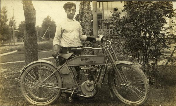 Dressed in his cycling outfit, Silas Wright Pifer poses next to his Harley-Davidson Motorcycle.