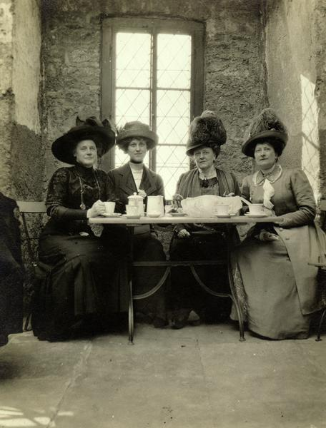 From left to right Ida Fisk, Dorothy Purchas (b. 1891), Emma (Thorsen) Purchas (1862-1944), and Ethelinda (Thorsen) Johnston (1856-1947) of Milwaukee, Wisconsin in Germany on vacation.  At this time Emma and Dorothy resided in England.  Wearing dresses and elaborate hats, the ladies are posed inside a rustic stone building having tea.  The photograph dates from 1910-1913.