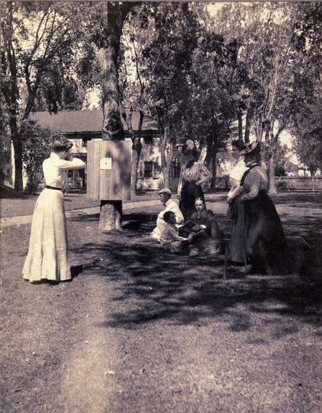 Target shooting on the east lawn of Villa Louis. Nina S. Dousman is on the extreme right of the image.