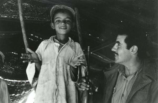 "An Algerian Bedouin boy with a soldier. The boy is pledging that he will kill his father ""with joy"" if the father should serve the French forces in the guerilla warfare. The soldier approving his declaration is from the FLN rebel Scorpion battalion to which Dickey Chapelle was attached."