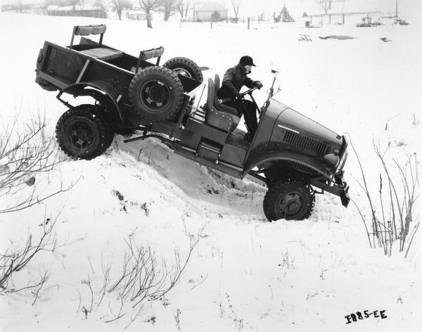 Man testing an International military M-2-4 4x4 truck on a snow-covered hill.