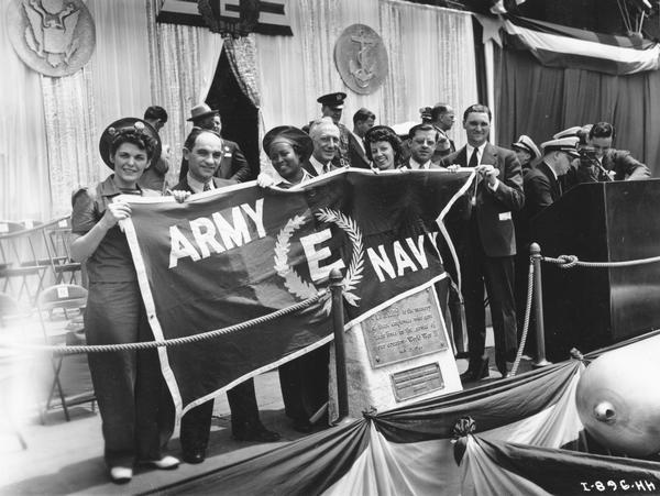 "Group of McCormick Works employees holding up Army-Navy ""E"" banner with torpedo in foreground. The McCormick Works was built by Cyrus McCormick in 1873 and became part of International Harvester in 1902. The factory was located at Blue Island and Western Avenues in the Chicago subdivision called ""Canalport."" It was closed in 1961."