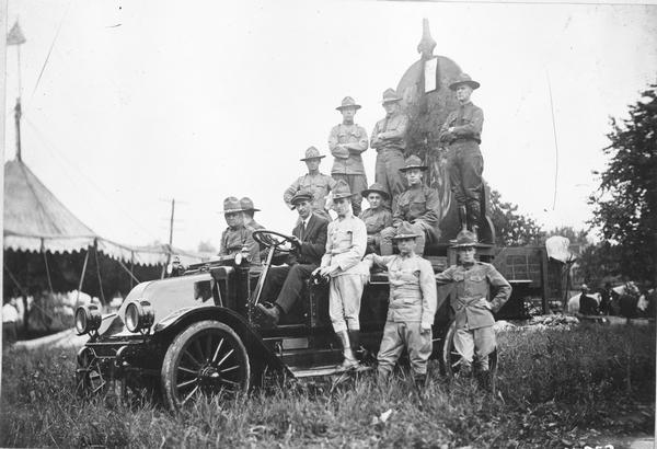 World War I soldiers on the back of an International truck with a recruiting poster.