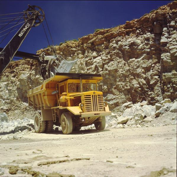 Color photograph of an International 65 payhauler dump truck in a quarry with shovel.