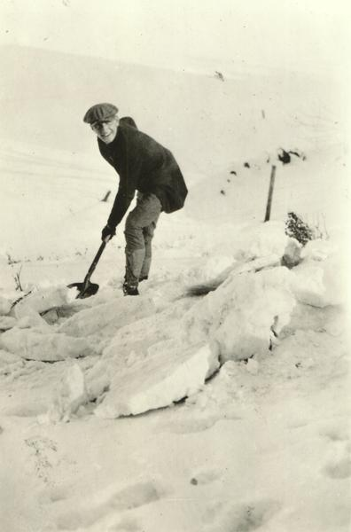Winter scene with Frederic March as a young man in a coat and hat, outdoors shoveling snow.
