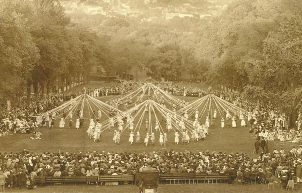 A view looking down on the Maypole Dance at the May Fete on Bascom Hill, showing dancers around four different Maypoles. In the foreground is the Lincoln Monument.