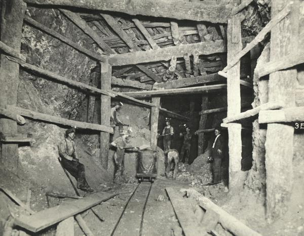 View inside a lead mine showing six miners with a car on a track.