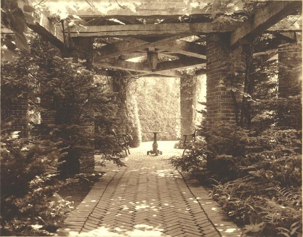 "The grounds at ""Walden,"" residence of the Cyrus McCormick, Jr. family, showing an outdoor table and two chairs."