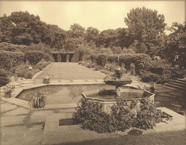 "The garage and garden at ""Walden,"" the estate of Cyrus McCormick, Jr., showing a fountain and pond in the foreground."