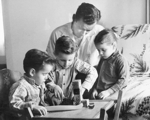 A father, Peter Froeming, watches as his three children George, Robert, and Roseann play with wooden blocks with small toy canoe in foreground.