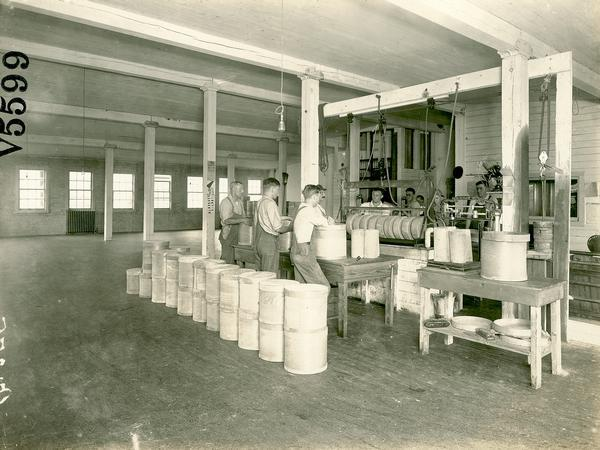 Workers paraffining cheese at the Sheboygan County Farmers' Coop cheese factory.