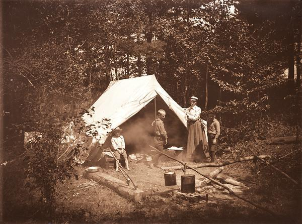 A family campsite with a woman and three boys standing next to a canvass wall tent.  In front of the tent is a campfire with pots and a log with hatchet and ax stuck in it.