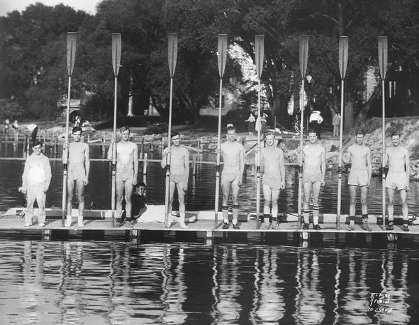 University of Wisconsin-Madison crew team holding their long oars, with coxswain on a pier on Lake Mendota.