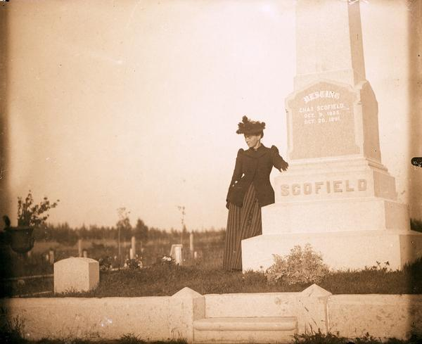 Cemetery monument of Charles Scofield.  A woman dressed in black stands next to the monument.