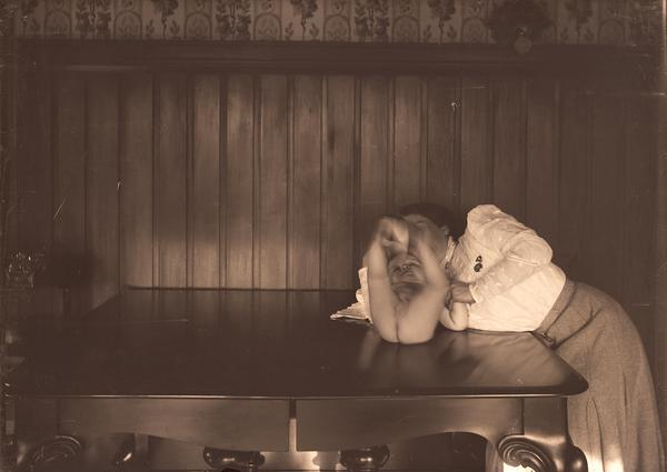A baby lies on the dining table playing with his feet while his mother looks on.