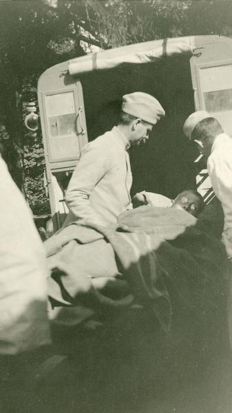 "Medical personnel load a wounded Prussian into an ambulance. Captioned: ""A wounded Prussian being loaded in my car for evacuation. He was shot just under his heart with an automatic, in a coup des mains (trench raid). Vaux Varennes."