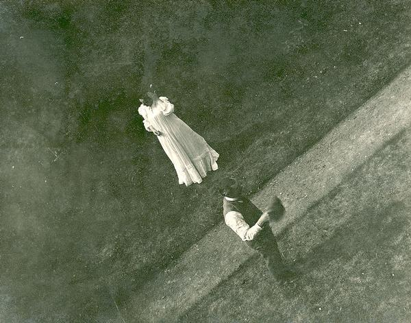 Overhead view of a man and woman on a pathway, she in white against a dark background, and he in shirt and vest.