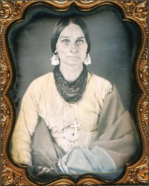 Quarter plate daguerreotype, waist-up portrait of Rachel Lawe Grignon, daughter of John Lawe and wife of Pierre Bernard Grignon. Wearing heavy bead necklace, earrings, and cross pendant, and wrapped in several blankets. Clothing and accessories are partly Native American style. Hand-tinted dress and blankets.