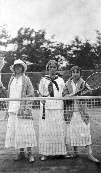 Elizabeth Hull, Elizabeth Baker, and Elizabeth Nisbet standing at the tennis court net at Coole Park Manor.