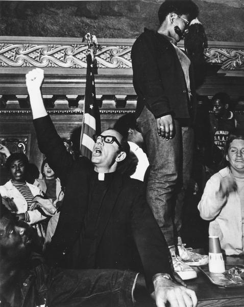 Father James Groppi with his fist in the air at the Wisconsin State Capitol during welfare demonstrations. He is surrounded by other protesters.