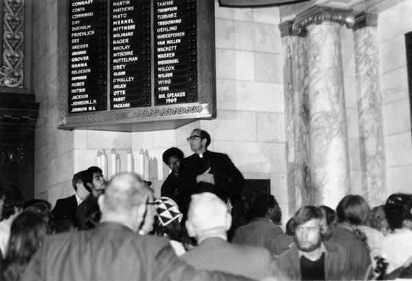 Father Groppi speaking at demonstration in the Wisconsin State Capitol Assembly Chamber.