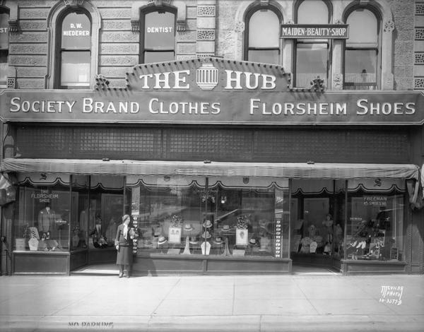 "Exterior of the Hub clothing store, located at 22-24 West Mifflin Street. A sign reads: ""Society Brand Clothes and Florsheim Shoes."" Second floor windows have signs that read: ""Dr. R.W. Niederer, Dentist"" and ""Maiden Beauty Shop."""